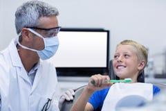 Οδοντίατρος που βοηθά το νέο ασθενή ενώ δόντια βουρτσών Στοκ Εικόνες