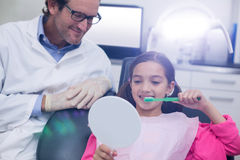 Οδοντίατρος που βοηθά το νέο ασθενή ενώ δόντια βουρτσών Στοκ Φωτογραφίες