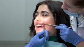 Οδοντίατρος που εγκαθιστά τα στηρίγματα δοντιών απόθεμα βίντεο