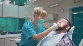 Οδοντίατρος που εξετάζει τα υπομονετικά δόντια ` s και που κοιτάζει στη κάμερα φιλμ μικρού μήκους