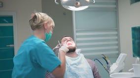 Οδοντίατρος που εξετάζει τα υπομονετικά δόντια ` s και που μιλά με τον steadicam απόθεμα βίντεο