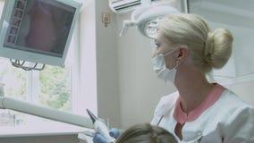 Οδοντίατρος που εξετάζει τα δόντια του ασθενή στο όργανο ελέγχου φιλμ μικρού μήκους