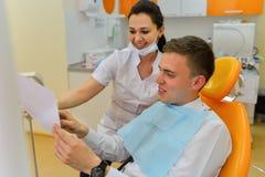 Οδοντίατρος που εξηγεί την των ακτίνων X εικόνα στον ασθενή Στοκ Εικόνα