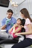 Οδοντίατρος που καθησυχάζει το εκφοβισμένο κορίτσι πριν από τον έλεγχο επάνω Στοκ εικόνα με δικαίωμα ελεύθερης χρήσης