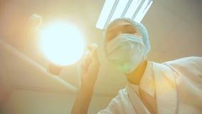 Οδοντίατρος που κρατά τον οδοντικούς λαμπτήρα και τα εργαλεία απόθεμα βίντεο