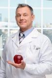 Οδοντίατρος που κρατά το κόκκινο μήλο Στοκ Εικόνα