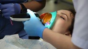Οδοντίατρος που μεταχειρίζεται το τα υπομονετικά δόντια ` s με τα οδοντικά εργαλεία στην οδοντική κλινική οδοντιατρική απόθεμα βίντεο