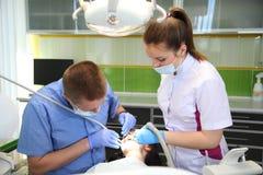 Οδοντίατρος που μεταχειρίζεται το τα υπομονετικά δόντια ` s με τα οδοντικά εργαλεία στην οδοντική κλινική οδοντιατρική Στοκ Εικόνες
