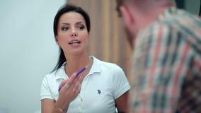 Οδοντίατρος που μιλά με έναν πελάτη στην υποδοχή απόθεμα βίντεο