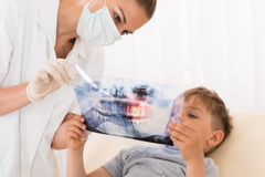 Οδοντίατρος που παρουσιάζει ακτίνα X δοντιών στον ασθενή παιδιών στοκ φωτογραφίες