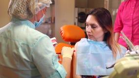 Οδοντίατρος που παρουσιάζει στον ασθενή πώς να βουρτσίσει τα δόντια δεξιά απόθεμα βίντεο