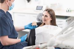 Οδοντίατρος που παρουσιάζει typodont στον εύθυμο ασθενή Στοκ φωτογραφίες με δικαίωμα ελεύθερης χρήσης