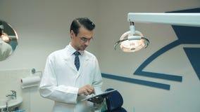 Οδοντίατρος που χρησιμοποιεί την ταμπλέτα στην οδοντική κλινική απόθεμα βίντεο