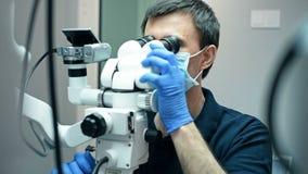Οδοντίατρος που χρησιμοποιεί το οδοντικό μικροσκόπιο απόθεμα βίντεο