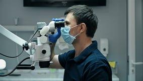 Οδοντίατρος που χρησιμοποιεί το οδοντικό μικροσκόπιο φιλμ μικρού μήκους