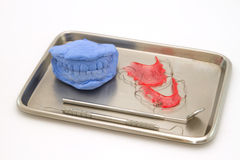 Οδοντικά πρότυπα γύψου και οδοντικό στήριγμα στον ιατρικό δίσκο στοκ εικόνες