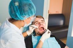 Οδοντική έννοια προσοχής Η οδοντική επιθεώρηση δίνεται στο όμορφο άτομο που περιβάλλεται από τον οδοντίατρο Στοκ φωτογραφία με δικαίωμα ελεύθερης χρήσης