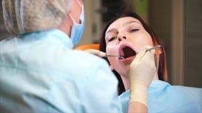 οδοντική διαδικασία Θηλυκός γιατρός ασθενών και οδοντιάτρων που εκτελεί την εξέταση φιλμ μικρού μήκους