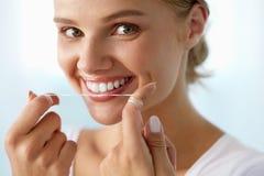 Οδοντική προσοχή Γυναίκα με το όμορφο χαμόγελο που χρησιμοποιεί το νήμα για τα δόντια Στοκ Εικόνα