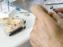 Οδοντικός τεχνικός που κάνει μια δομή μετάλλων μιας οδοντικής κορώνας ή Στοκ φωτογραφία με δικαίωμα ελεύθερης χρήσης