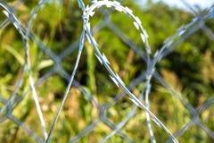 Οδοντωτός - καλώδιο του φράκτη που προστατεύει τα σύνορα μεταξύ της Ουγγαρίας α Στοκ Εικόνα