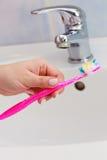 Οδοντόβουρτσα εκμετάλλευσης χεριών στο λουτρό Στοκ Φωτογραφίες