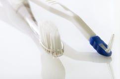 Οδοντόβουρτσα και χοντροσκαλίδρα στον άσπρο πίνακα Στοκ Εικόνα