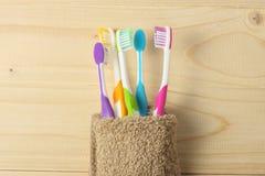 Οδοντόβουρτσα οδοντοβουρτσών με την πετσέτα λουτρών στον ξύλινο πίνακα Τοπ άποψη με το διάστημα αντιγράφων στοκ φωτογραφία
