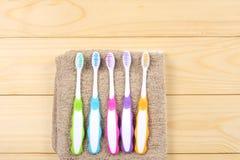 Οδοντόβουρτσα οδοντοβουρτσών με την πετσέτα λουτρών στον ξύλινο πίνακα Τοπ άποψη με το διάστημα αντιγράφων στοκ φωτογραφίες