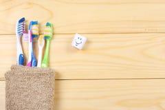 Οδοντόβουρτσα οδοντοβουρτσών με την πετσέτα λουτρών στον ξύλινο πίνακα Τοπ άποψη με το διάστημα αντιγράφων στοκ εικόνα