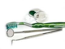 Οδοντόβουρτσες, οδοντικό νήμα και ένας καθρέφτης στο λευκό Στοκ φωτογραφίες με δικαίωμα ελεύθερης χρήσης
