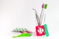 Οδοντόβουρτσες στο γυαλί στα άσπρα εργαλεία υποβάθρου για τη στοματική φροντίδα Στοκ εικόνα με δικαίωμα ελεύθερης χρήσης