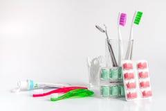 Οδοντόβουρτσες στο γυαλί στα άσπρα εργαλεία υποβάθρου για τη στοματική φροντίδα Στοκ Εικόνα