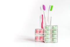 Οδοντόβουρτσες στο γυαλί στα άσπρα εργαλεία υποβάθρου για τη στοματική φροντίδα Στοκ φωτογραφία με δικαίωμα ελεύθερης χρήσης