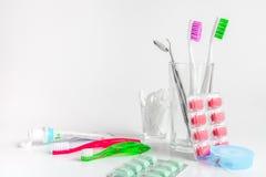 Οδοντόβουρτσες στο γυαλί στα άσπρα εργαλεία υποβάθρου για τη στοματική φροντίδα Στοκ Φωτογραφία