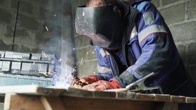 Ο οξυγονοκολλητής πλάγιας όψης στη μάσκα συγκόλλησης ενώνει στενά δύο μέρη μετάλλων Ο εργάτης στις φόρμες εργάζεται στο εσωτερικό φιλμ μικρού μήκους