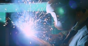 Ο οξυγονοκολλητής στη μάσκα συγκόλλησης, στα λειτουργώντας ενδύματα στο εργοστάσιο, ενώνει στενά το σωλήνα στο δωμάτιο εργοστασίω φιλμ μικρού μήκους