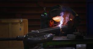 Ο οξυγονοκολλητής στη μάσκα συγκόλλησης, στα λειτουργώντας ενδύματα στο εργοστάσιο, ενώνει στενά το σωλήνα στο δωμάτιο εργοστασίω