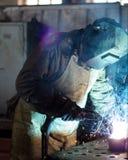 Ο οξυγονοκολλητής στο εργοστάσιο σε μια μάσκα συγκόλλησης ενώνει στενά τα μέρη, τη συγκόλληση και τους σπινθήρες μετάλλων στοκ φωτογραφία με δικαίωμα ελεύθερης χρήσης