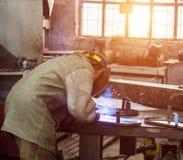 Ο οξυγονοκολλητής στο προστατευτικό κοστούμι στο εργοστάσιο ενώνει στενά τα μέρη, εργαστήριο, ηλιοβασίλεμα στοκ εικόνα