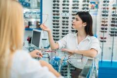 Ο οπτικός και ο καταναλωτής θηλυκών επιλέγουν το πλαίσιο γυαλιών στοκ εικόνες