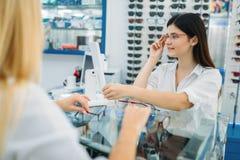 Ο οπτικός και ο καταναλωτής θηλυκών επιλέγουν το πλαίσιο γυαλιών στοκ φωτογραφία με δικαίωμα ελεύθερης χρήσης
