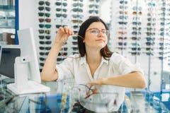 Ο οπτικός και ο καταναλωτής θηλυκών επιλέγουν το πλαίσιο γυαλιών στοκ φωτογραφία