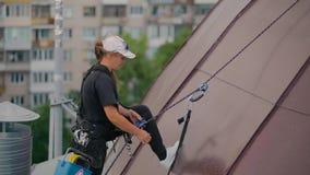 Ο ορειβάτης γυναικών ελέγχει την ασφάλεια της εξάρτησης φιλμ μικρού μήκους