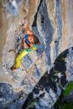 Ο ορειβάτης κοριτσιών αναρριχείται στο βράχο στοκ φωτογραφία