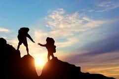 Ο ορειβάτης φτάνει στο συνεργάτη του με τη βοήθεια του ενός τον άλλον στοκ φωτογραφία με δικαίωμα ελεύθερης χρήσης
