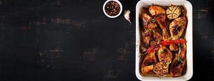 Ο ορεκτικός φούρνος έψησε τα χρυσά τυμπανόξυλα κοτόπουλου σε ένα πιάτο ψησίματος σε έναν σκοτεινό πίνακα στοκ εικόνες