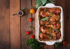 Ο ορεκτικός φούρνος έψησε τα χρυσά τυμπανόξυλα κοτόπουλου σε ένα πιάτο ψησίματος σε έναν ξύλινο πίνακα στοκ εικόνα με δικαίωμα ελεύθερης χρήσης
