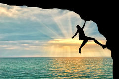 Ο ορεσίβιος αναρριχείται στον απότομο βράχο πέρα από το ηλιοβασίλεμα θάλασσας Στοκ εικόνα με δικαίωμα ελεύθερης χρήσης