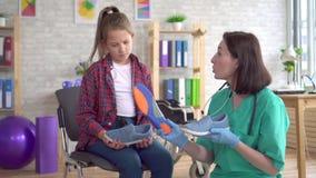 Ο ορθοπεδικός γιατρός λέει σε ένα έφηβη για τις ορθοπεδικές μετζεσόλες απόθεμα βίντεο